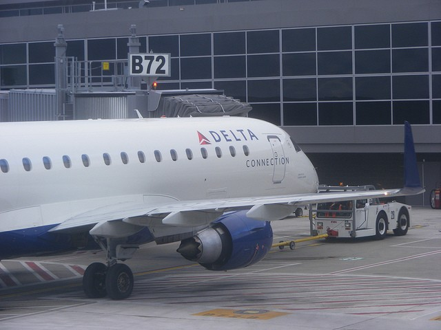 A tug pulls a Delta Connection jet to a gate at Washington Dulles International Airport. Photo by Benét J. Wilson