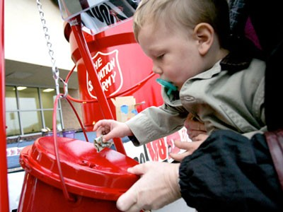 Baby putting money in Salvation Army bucket