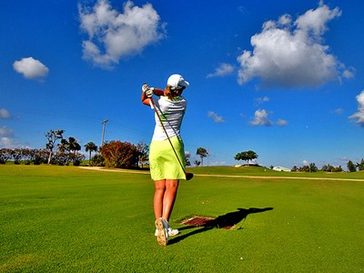 woman in yellow skirt on green golf course, blue sky