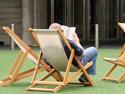 Guy reading a book in deck chair