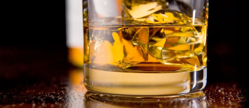 Scotch Whiskey on the rocks in a glass amber