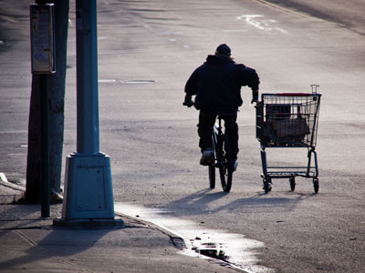 Man on bile with scrap metal in grocery basket