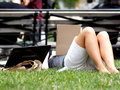 woman lying in park with laptop open
