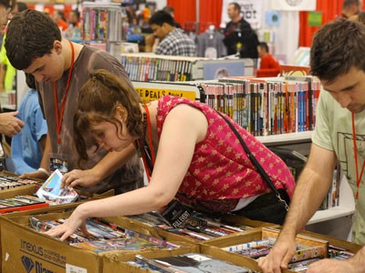People looking through boxes of comic books.