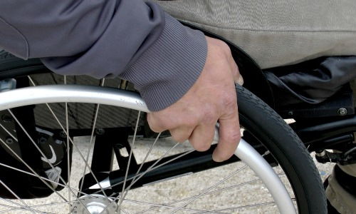 Closeup of a hand on a wheelchair.