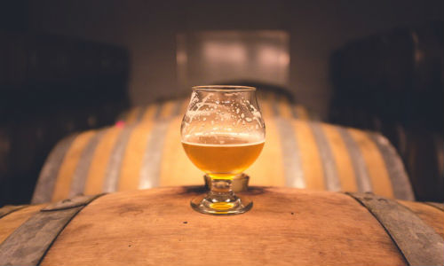 "Is that craft beer really an indie? Craft brewers hope to distinguish themselves from bigger brewers by declaring their ownership on the bottle. (""Focus Photography of Footed Glass Half Full"" photo courtesy of Pexels)."