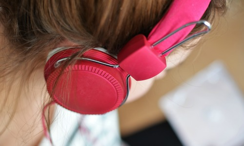 """Recent data show an estimated 112 million Americans have ever listened to a podcast. (""""Woman wearing headphones"""" image via Pexels user breakingpic CC0 License)"""