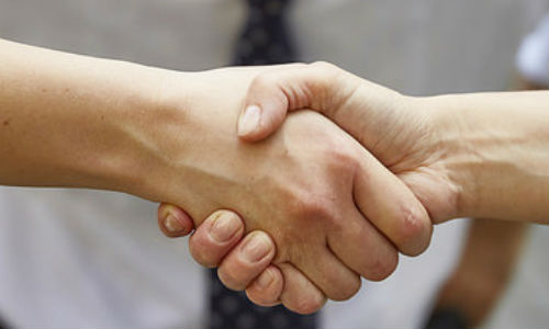 "Trust is a the heart of the DOL's new fiduciary rule. Here are three big stories to develop for your readers. (""Handshake with smile"" by Vilmos Vincze via Flicker, CC BY 2.0)"