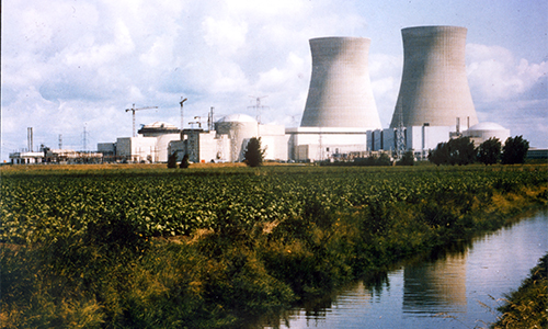 Two power plants sit by a river in Doel, Belgium.