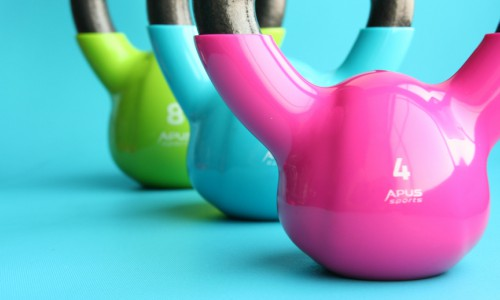 Multi-colored kettle bell weights in a row
