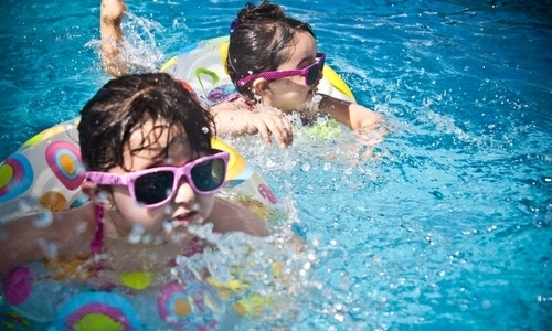 two little girls wearing sunglasses in a swimming pool
