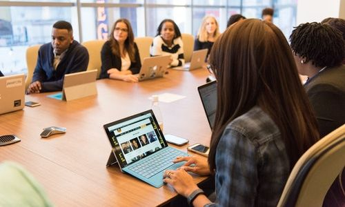 people sitting at a conference table with laptops